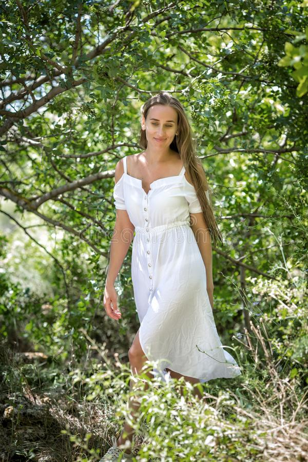Menina no vestido branco na floresta decíduo fotografia de stock