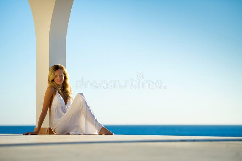 Menina no vestido branco no por do sol pelo mar 3 imagem de stock