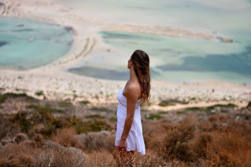A menina no vestido branco olha a lagoa da praia de Balos, Creta imagem de stock