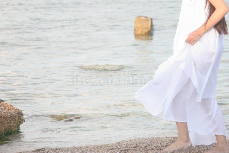 Menina no vestido branco que anda ao longo do litoral imagens de stock