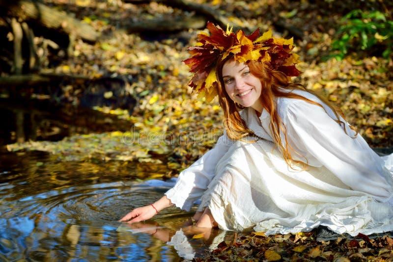 Menina no vestido branco que senta-se e que joga perto da água em uma grinalda das folhas amarelas foto de stock