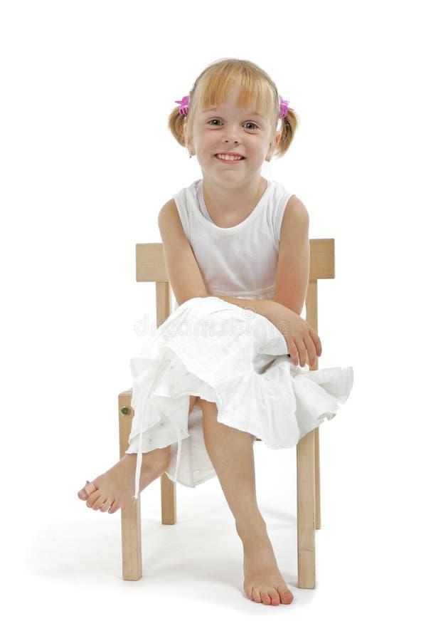 Menina no vestido branco que senta-se na cadeira de madeira fotografia de stock