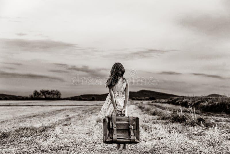 Menina no vestido clássico com mala de viagem do curso foto de stock