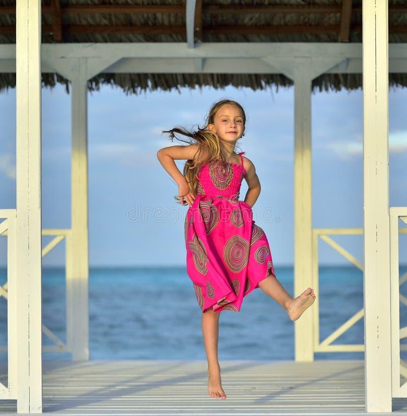 Menina no vestido colorido que salta e que dança no cais de madeira branco perto do oceano fotos de stock