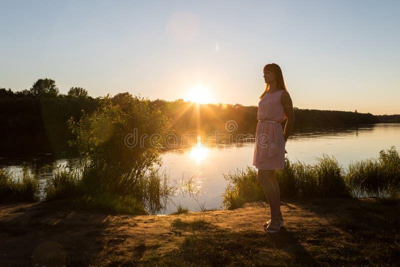 Menina no vestido cor-de-rosa na praia do rio durante o por do sol Fundo exterior do retrato e do sol imagens de stock royalty free