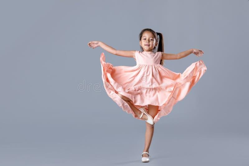 Menina no vestido cor-de-rosa que levanta no fundo cinzento foto de stock royalty free