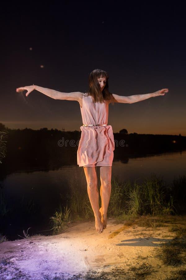 Menina no vestido cor-de-rosa que salta na praia do rio durante o por do sol e a farinha branca na terra imagens de stock royalty free