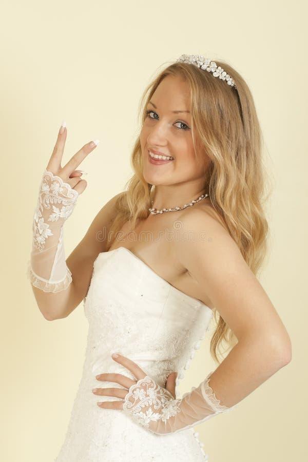 Menina no vestido da noiva com o braço levantado fotos de stock royalty free