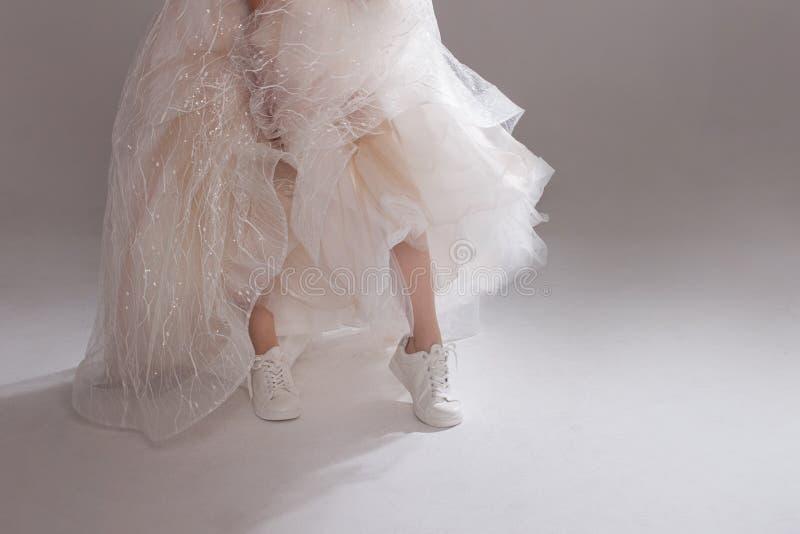 A menina no vestido de casamento magnífico e nas sapatilhas brancas, close-up dos pés Noiva do fugitivo imagem de stock