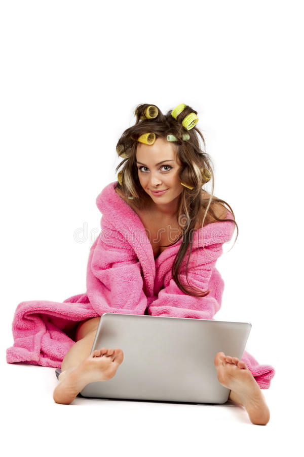 Menina no vestido de limpeza cor-de-rosa que senta-se com portátil imagem de stock royalty free