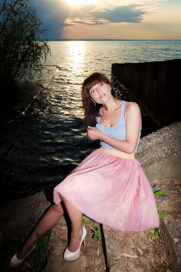 Menina no vestido do verão cercado pelas hortaliças que correm ao longo da água imagem de stock