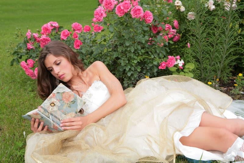 A menina no vestido dourado leu o livro imagem de stock