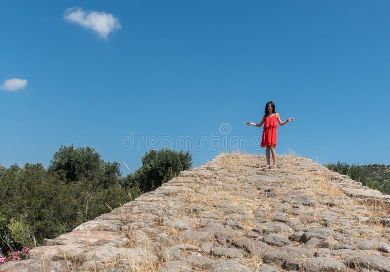 A menina no vestido e em óculos de sol vermelhos com mãos guardou para fora estar sobre imagem de stock royalty free