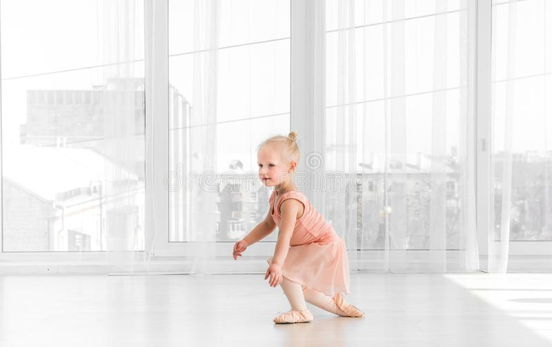 A menina no vestido e no pointe peachy calça a dança na sala fotos de stock