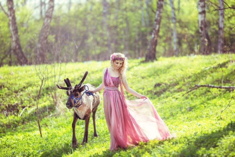 Menina no vestido feericamente com um trem de fluxo do vestido que anda com uma rena fotos de stock royalty free