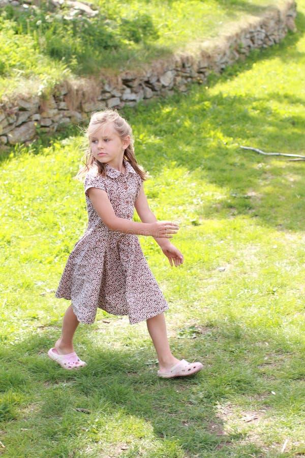 Menina no vestido florescido que olha para trás fotografia de stock
