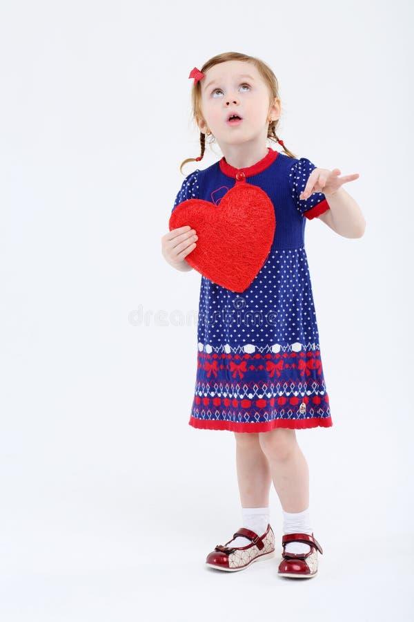 A menina no vestido guarda o coração vermelho e olha acima imagens de stock