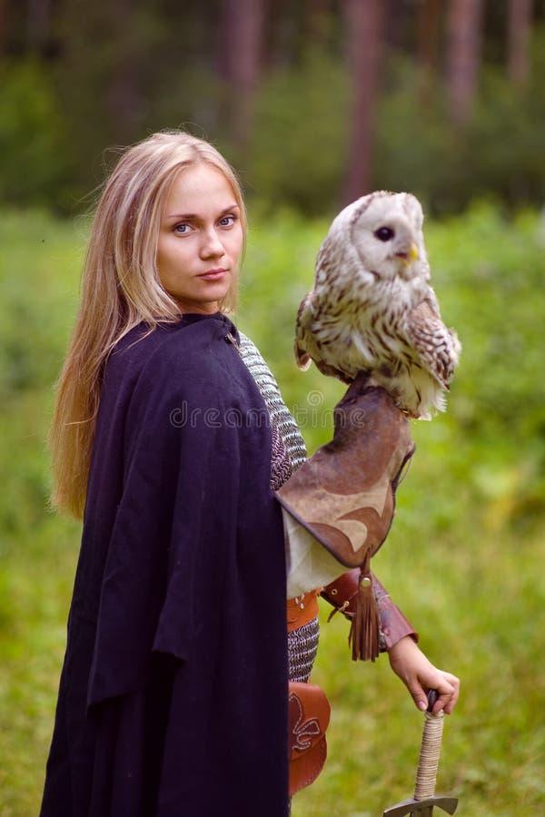 Menina no vestido medieval com uma espada que guarda uma coruja fotografia de stock
