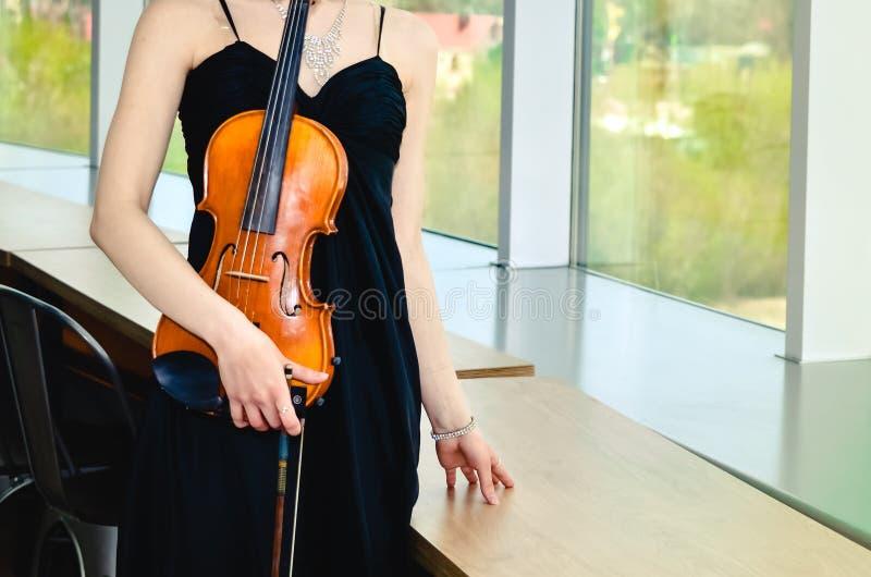 Menina no vestido preto com as correias com violino marrom imagem de stock
