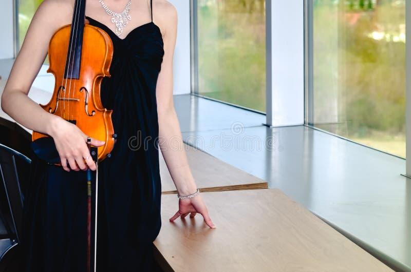 Menina no vestido preto com as correias com violino marrom fotografia de stock