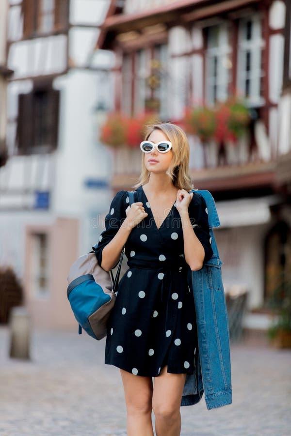 Menina no vestido preto que anda abaixo da rua em Strasbourg fotografia de stock royalty free