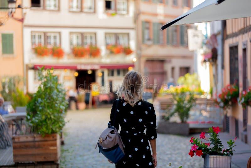 Menina no vestido preto que anda abaixo da rua em Strasbourg fotos de stock royalty free