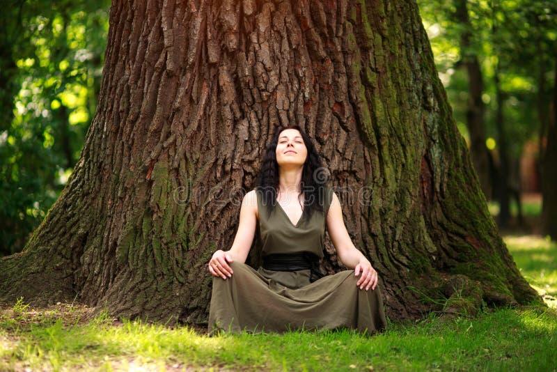 A menina no vestido senta-se apreciando a natureza medita, ioga das práticas na floresta fotos de stock royalty free