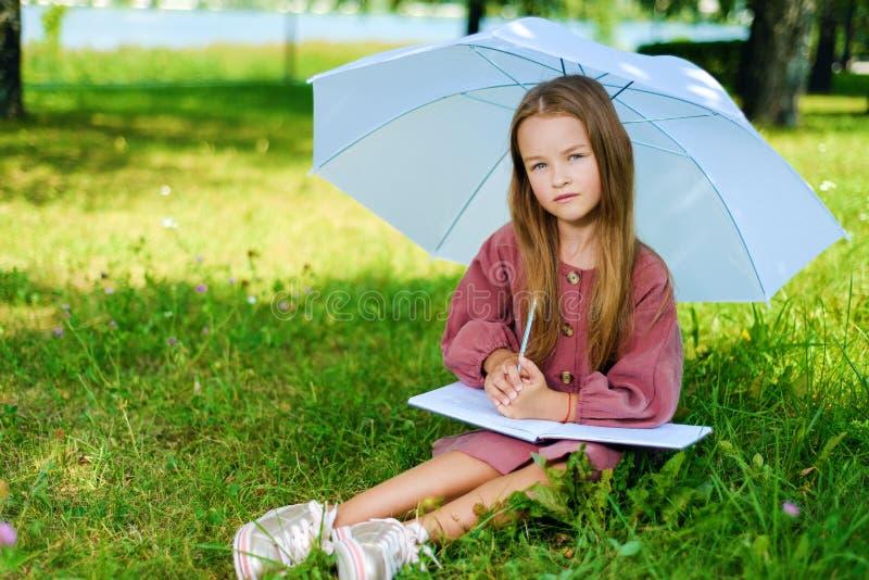 A menina no vestido senta-se no parque na grama no dia ensolarado brilhante imagens de stock royalty free