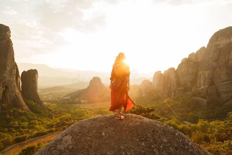 Menina no vestido vermelho do voo que olha o por do sol majestoso no vale de Meteora, Grécia fotografia de stock