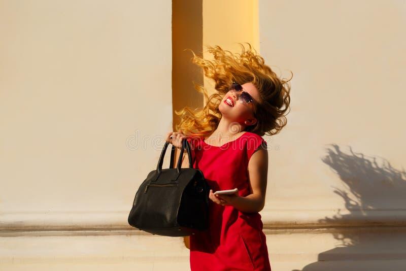 Menina no vestido vermelho e com bolsa na moda, telefone imagens de stock
