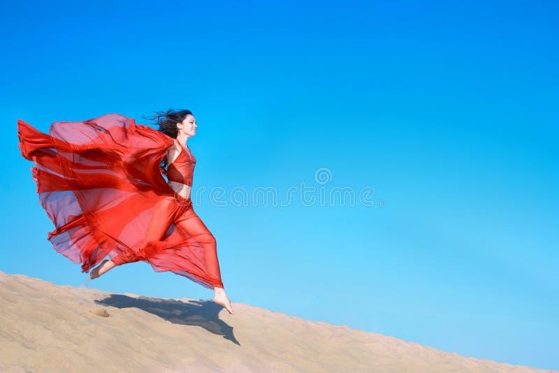 Menina no vestido vermelho pairoso que corre em dunas de areia fotos de stock