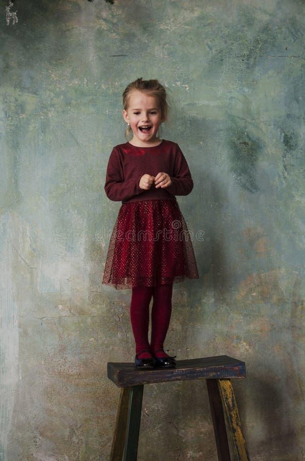 Menina no vestido vermelho que está na cadeira de madeira e no sorriso imagens de stock royalty free