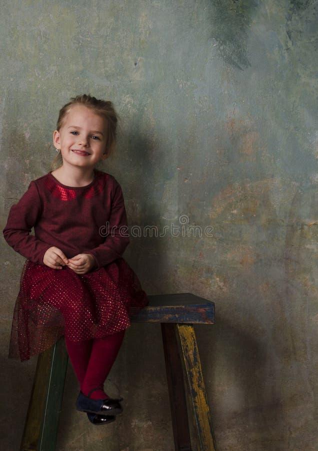 Menina no vestido vermelho que senta-se na escada de madeira e no sorriso imagem de stock royalty free