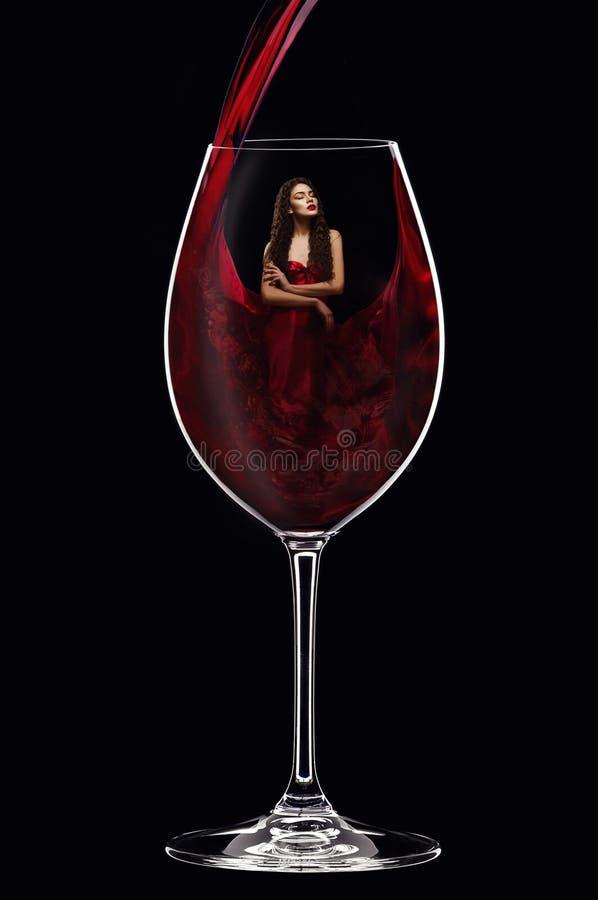 Menina no vidro de vinho interno do vestido vermelho fotos de stock royalty free