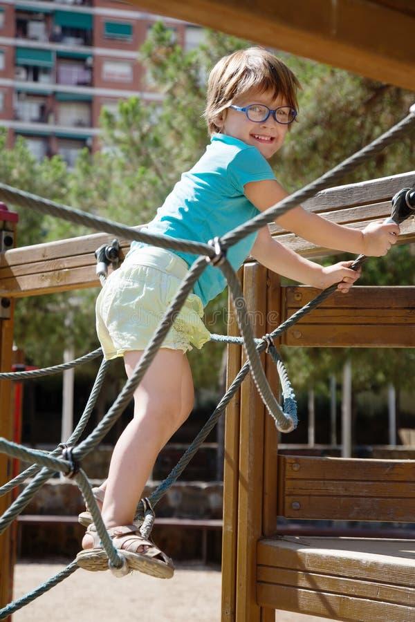 Menina no vidro no campo de jogos ação-orientado fotos de stock royalty free
