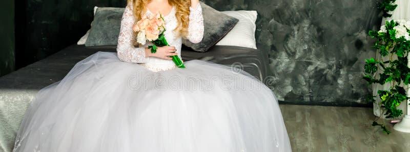 Menina-noiva em um vestido de casamento com um objeto em suas mãos foto de stock royalty free