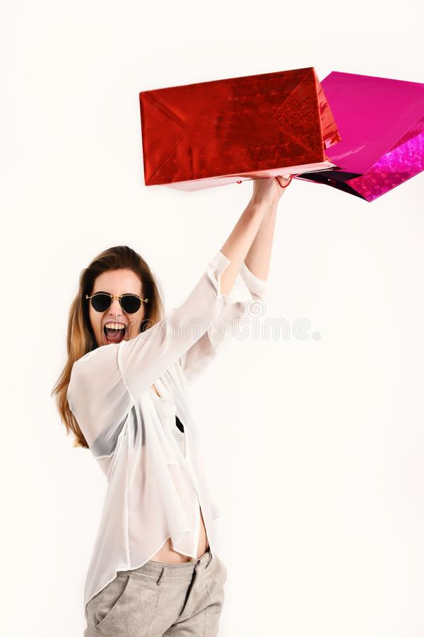 Menina nos óculos de sol com a cara alegre isolada no fundo branco A senhora guarda sacos de compras vermelhos e cor-de-rosa Mulh fotos de stock royalty free