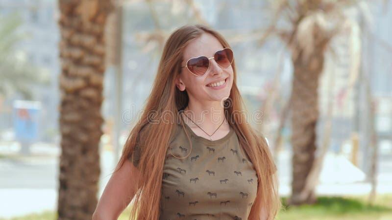 Menina nos óculos de sol no fundo de árvores das ruas e de palmas de Dubai fotos de stock royalty free
