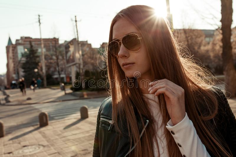 Menina nos óculos de sol no fundo do por do sol e da azáfama da cidade foto de stock