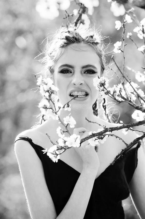 A menina nos dentes apoia comer a florescência branca da flor da mola da cereja foto de stock