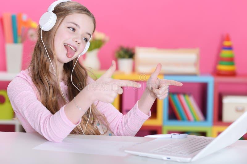 Menina nos fones de ouvido com portátil foto de stock