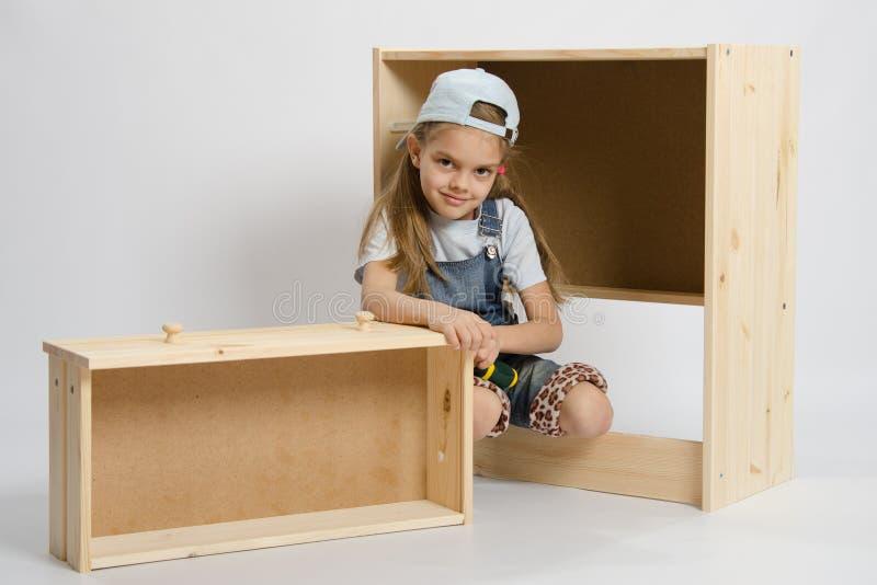 A menina nos macacões senta-se ao lado dos elementos da mobília do lixo fotografia de stock