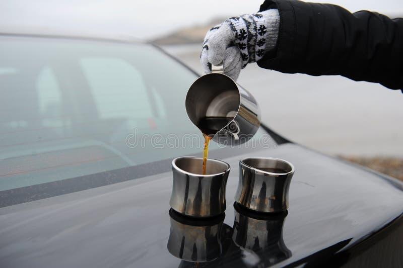 A menina nos mitenes derrama o café do jarro nos copos no tronco de carro r imagens de stock