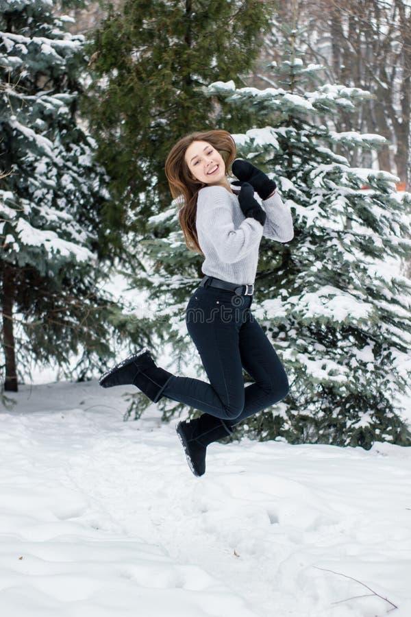 Menina nos mitenes no fundo de árvores de Natal fotografia de stock royalty free