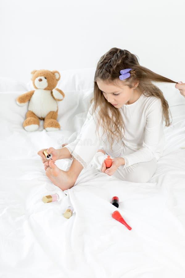 Menina nos pijamas e nos encrespadores que aplicam o verniz para as unhas às unhas do pé que sentam-se na cama imagem de stock royalty free