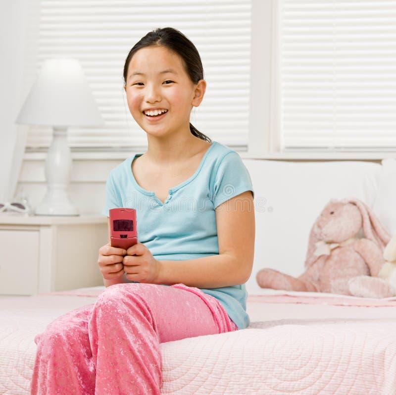 Menina nos pijamas no envio de mensagem de texto do quarto imagens de stock