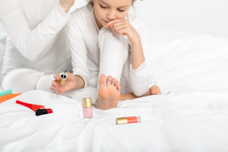 Menina nos pijamas que aplicam o verniz para as unhas às unhas do pé na cama fotos de stock