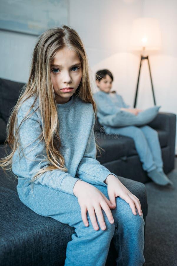 Menina nos pijamas que olham a câmera quando irmão mais novo que senta-se atrás fotografia de stock