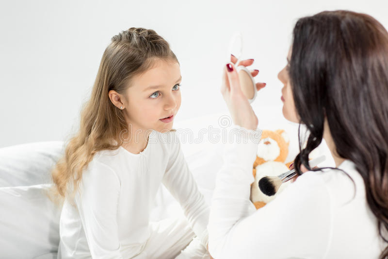 Menina nos pijamas que olham a mãe com espelho cosmético imagem de stock royalty free