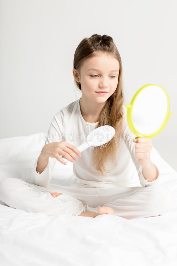 Menina nos pijamas que sentam-se na cama e que penteiam o cabelo foto de stock
